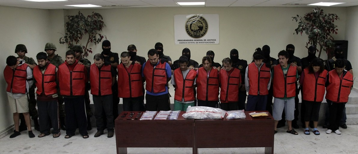 Police detectives escort members of the Zetas drug gang as they are presented to the media in Monterrey October 15, 2012. The Mexican army and the State Agency of Investigations (AEI) presented 16 members of the Zetas drug gang detained in several operations in the metropolitan area of Monterrey between last September and October, local media reported. The detainees are responsible for murder, drug trafficking and kidnapping. REUTERS/Daniel Becerril