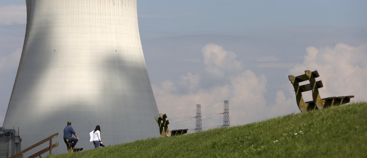 People look at the cooling towers of Doel's nuclear plant in northern Belgium August 20, 2014. Two Belgian nuclear reactors owned by GDF-Suez unit Electrabel may remain offline until spring and may need to be halted permanently, Belgian state broadcaster VRT reported on Tuesday. The Belgian nuclear regulator ordered production to be stopped at the 1,008 megawatt Tihange 2 reactor and the 1,006 megawatt Doel 3 reactor in 2012 after finding indications of cracks in their core tanks. Electrabel was not immediately available for comment.  REUTERS/Francois Lenoir