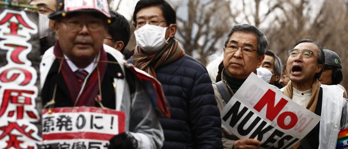 Protesters hold placards during an anti-nuclear energy rally in central Tokyo March 8, 2015. Anti-nuclear activists took to the streets on Sunday in Tokyo denouncing a planned restart of the country's nuclear reactors ahead of the fourth anniversary of the March 11, 2011 earthquake and tsunami disaster. REUTERS/Thomas Peter