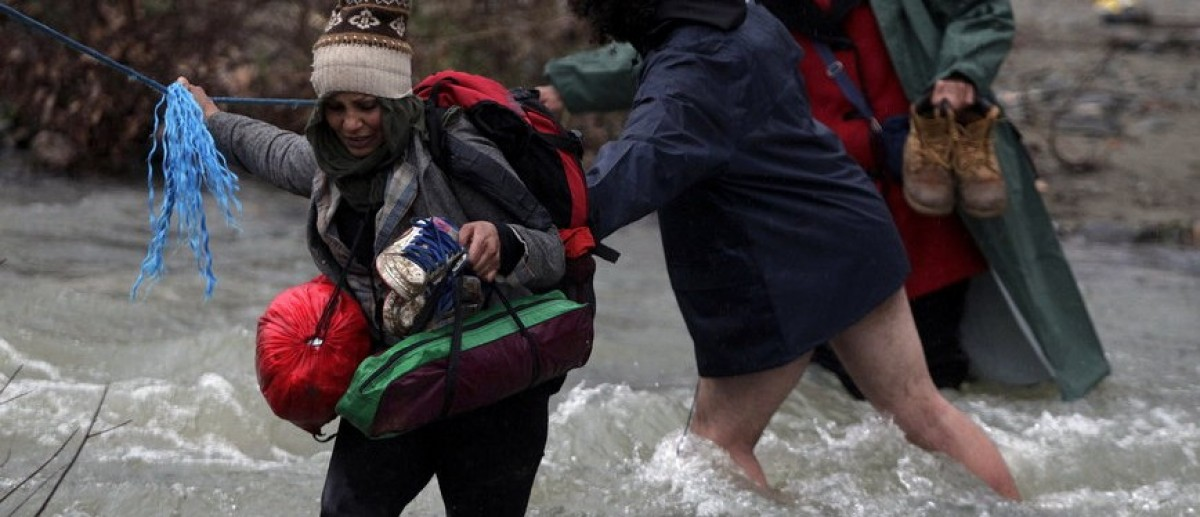 Refugees and migrants cross a river near the Greek-Macedonian border to return to Greece, after an unsuccessful attempt to enter Macedonia, west of the village of Idomeni, Greece, March 15, 2016. REUTERS/Alexandros Avramidis