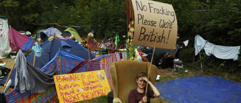 Local resident Kip Parker demonstrates as police escort a lorry to the drill entrance of a site run by Cuadrilla Resources, in the village of Balcombe in southern England September 3, 2013. Caudrilla Resources's site in the village of Balcombe in rural West Sussex has become a focal point for protesters who oppose fracking, a technique the company has pioneered in the search for shale gas in Britain. REUTERS/Luke MacGregor (BRITAIN)