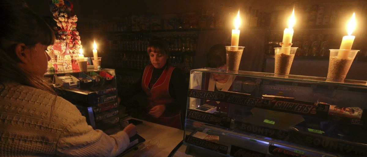 A customer visits a grocery lit with candles due to a power cut, in Simferopol, Crimea, November 22, 2015. (REUTERS/Pavel Rebrov)