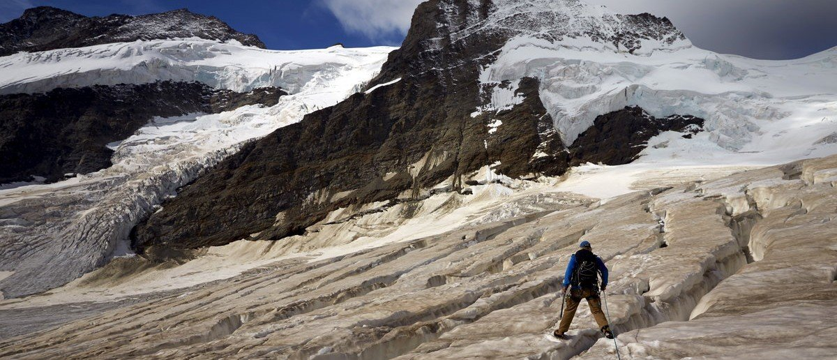 Mountain guide Christian Pletscher walks towards the Aletsch Glacier from the Jungfraufirn Glacier, Switzerland, August 28, 2015. One of Europe's biggest glaciers, the Great Aletsch coils 23 km (14 miles) through the Swiss Alps - and yet this mighty river of ice could almost vanish in the lifetimes of people born today because of climate change. The glacier, 900 metres (2,950 feet) thick at one point, has retreated about 3 km (1.9 miles) since 1870 and that pace is quickening.  REUTERS/Denis Balibouse