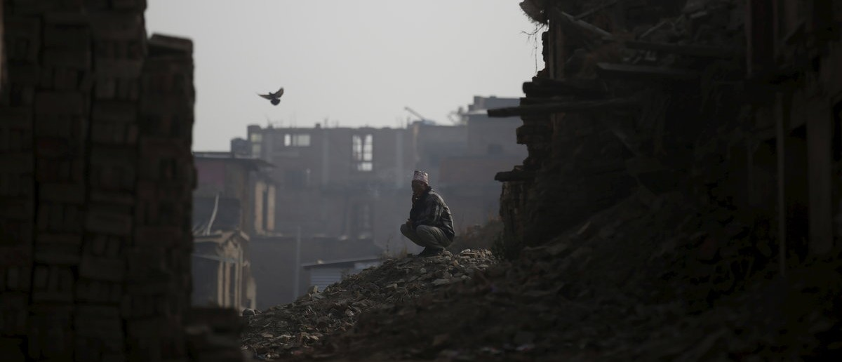 A man smokes a cigarette while sitting on top of the debris of houses damaged during the earthquake last year in Bhaktapur, Nepal, January 29, 2016. Twin earthquakes in April and May 2015 killed almost 9,000 people in Nepal's worst natural disaster. REUTERS/Navesh Chitrakar