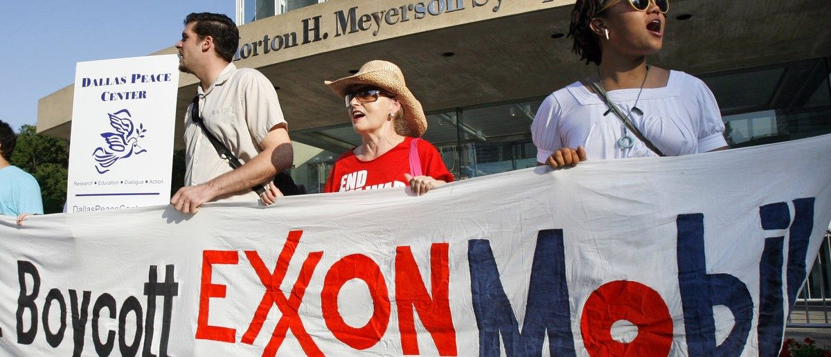 Meg Bell (R) holds a banner during a protest before the start of the Exxon Mobil Corporation Shareholders Meeting in Dallas, Texas, May 28, 2008.  REUTERS/Mike Stone