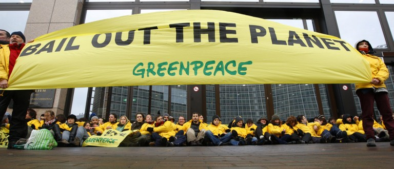 """Greenpeace activists bar the entry to European Union headquarters in Brussels March 10, 2009, urging finance ministers inside to bail out the planet and devote billions of euros to help poor nations tackle climate change. """"Save the climate, bail out the planet,"""" chanted the group of around 100 protesters who chained themselves to the gates outside the EU Council, where ministers were discussing how much the bloc should contribute to this climate fund. REUTERS/Yves Herman"""