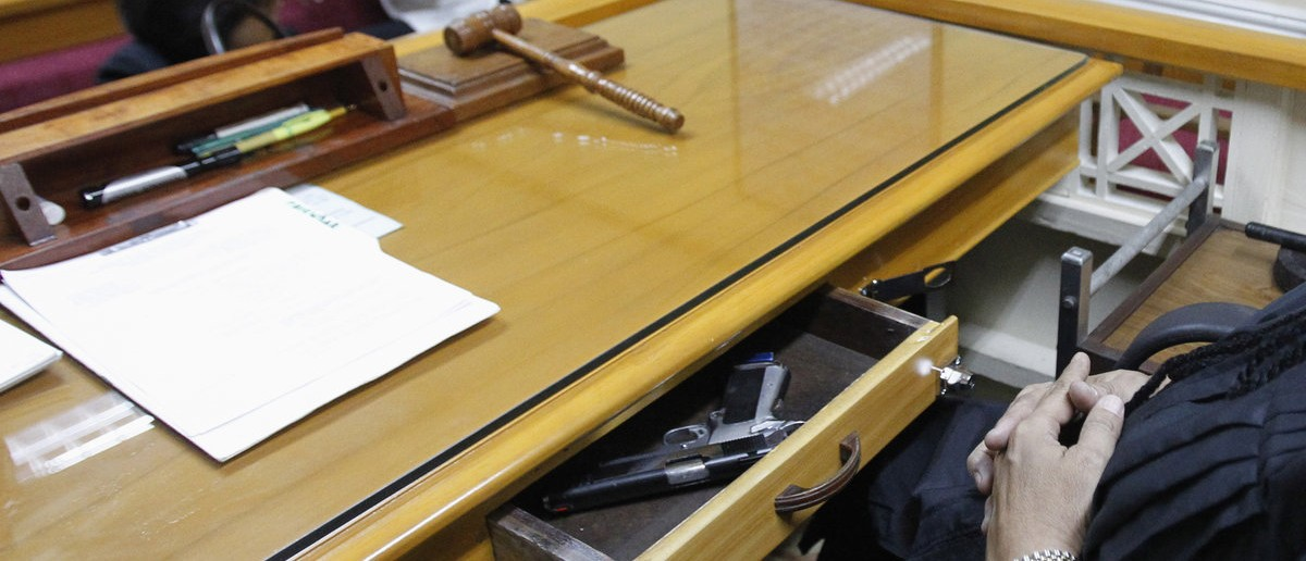 "Jaime ""Jimmy"" Santiago, a lower court judge in Manila, keeps his drawer open containing his service pistol while hearing a case at his sala at the Regional Trial Court branch 3 at city hall in Manila March 5, 2013. Santiago, a former police officer who headed a special weapons and tactics (SWAT) unit, favours arming Filipino judges to protect themselves from disgruntled litigants who can't accept decisions and criminal syndicates whose members were sent to jail. There had been cases of shootings inside courtrooms. REUTERS/Romeo Ranoco"