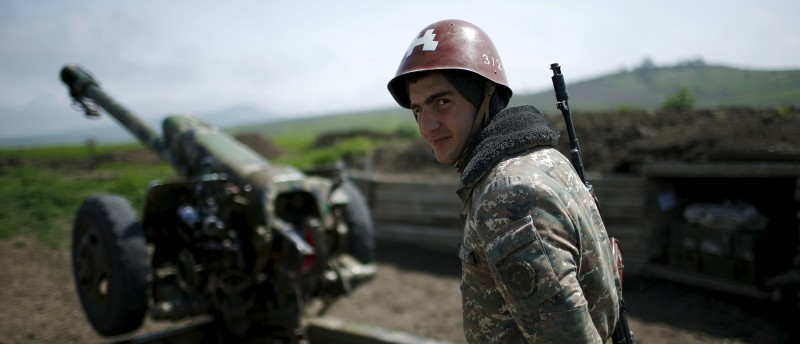 An ethnic Armenian soldier stands next to a cannon at the artillery positions near Nagorno-Karabakh's town of Martuni