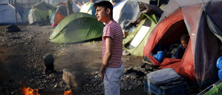 A boy warms up at a fire at a makeshift camp for migrants and refugees at the Greek-Macedonian border near the village of Idomeni, Greece, April 10, 2016. REUTERS/Stoyan Nenov