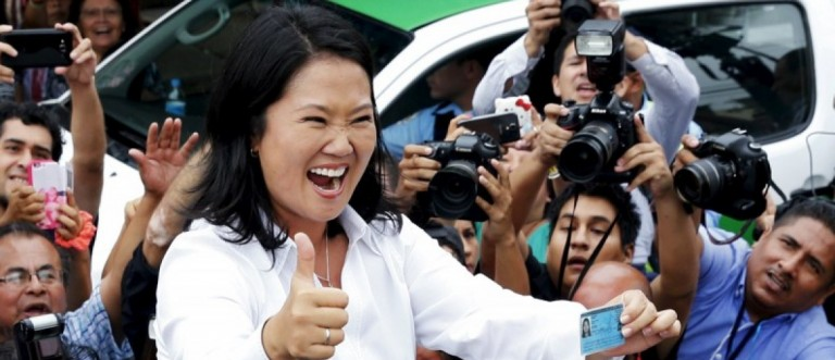 Peru's presidential candidate Keiko Fujimori waves to supporters and press after voting at presidential election in Lima