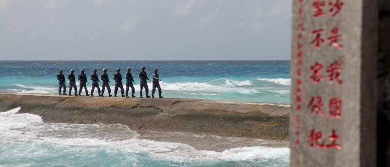 Soldiers of China's People's Liberation Army (PLA) Navy patrol near a sign in the Spratly Islands, known in China as the Nansha Islands