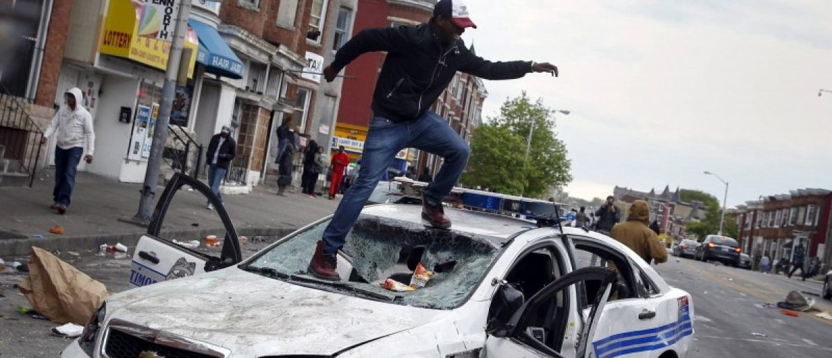 Demonstrators jump on a damaged Baltimore police department vehicle during clashes in Baltimore, Maryland, in this file photo taken April 27, 2015.  REUTERS/Shannon Stapleton