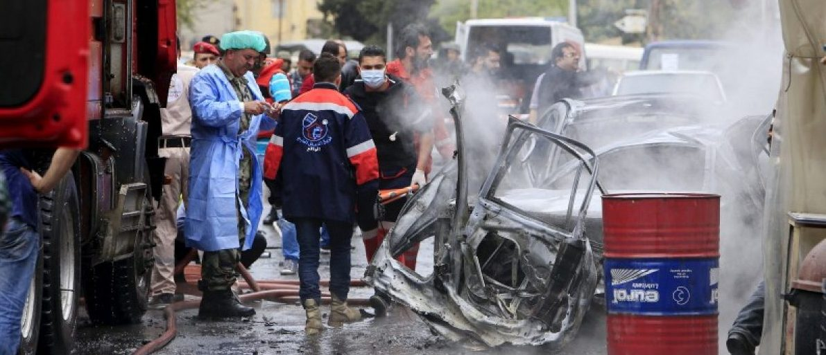 Security and civil defense members inspect a car wreck after an explosion that killed Fathi Zaydan, a Fatah official responsible for the Palestinian camp of Mieh Mieh in Sidon, near Ain al-Hilweh Palestinian refugee camp, near the port-city of Sidon