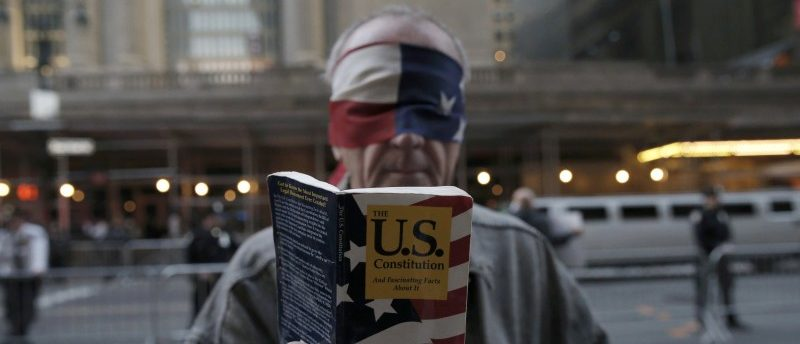 A blindfolded demonstrator holds up a copy of the United States Constitution while protesting against the Republican U.S. presidential candidate Donald Trump in midtown Manhattan in New York City, April 14, 2016. REUTERS/Mike Segar