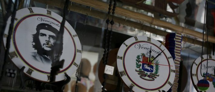 """Wall clocks with Venezuela's shield, with country map and with a portrait of Ernesto """"Che"""" Guevara are seen on a shelf at a store in Caracas"""