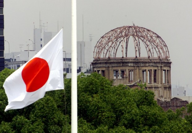The Japanese national flag flutters at half-mast in the foreground of the atomic bomb dome at the Hiroshima Peace Memorial Park, in western Japan