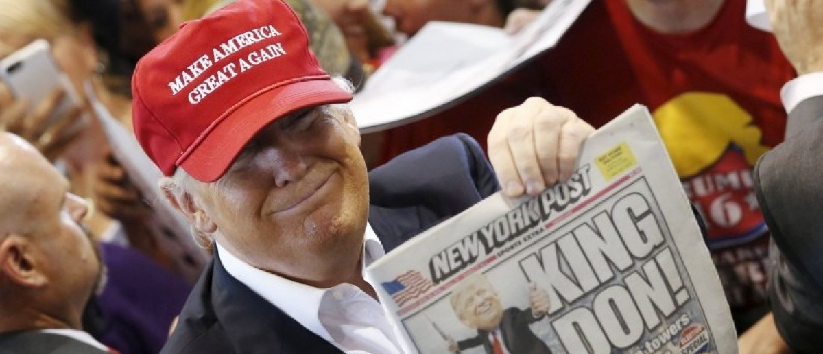 U.S. Republican presidential candidate Donald Trump holds up the front page of the New York Post as he signs autographs at a rally with supporters in Harrington, Delaware, U.S. April 22, 2016. REUTERS/Jonathan Ernst