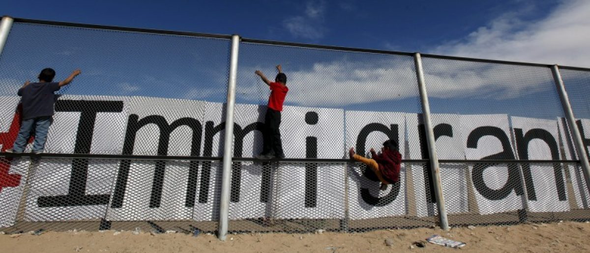 Children climb up the border fence between Ciudad Juarez and El Paso, USA, during a bi-national mass in support of migrants in Ciudad Juarez
