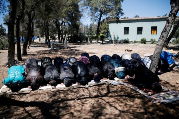 Men pray among trees at a camp for refugees and migrants in Schisto, near Athens