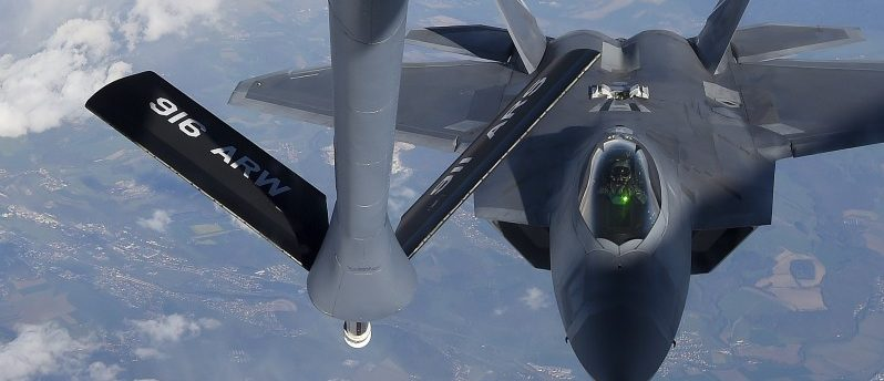A pilot looks up from a U.S. F-22 Raptor fighter at a fuel boom as it prepares to refuel in mid-air with a KC-135 plane over European airspace