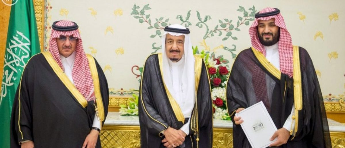 Saudi Crown Prince Mohammed bin Nayef, Saudi King Salman, and Saudi Arabia's Deputy Crown Prince Mohammed bin Salman stand together after Saudi Arabia's cabinet agrees to implement a broad reform plan known as Vision 2030 in Riyadh