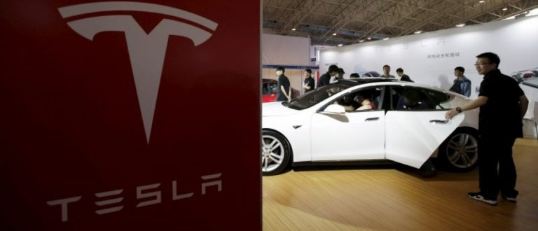 People visit a Tesla Model S car during the Auto China 2016 in Beijing, China, April 25, 2016.