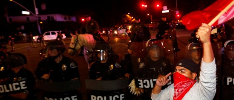 Police in riot gear form a line to break up a group of protesters outside Republican U.S. presidential candidate Donald Trump's campaign rally in Costa Mesa