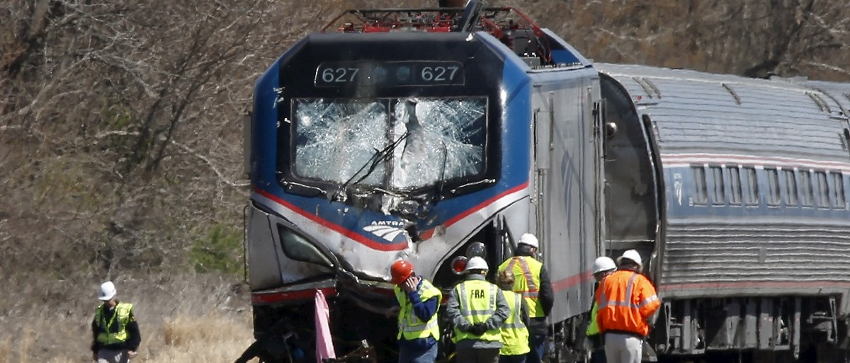 Emergency personnel examine the scene after an Amtrak passenger train struck a backhoe, killing two people, in Chester, Pennsylvania, April 3, 2016. The southbound Palmetto train running from New York to Savannah, Georgia, had about 341 passengers and seven crew members aboard when it struck the backhoe. REUTERS/Dominick Reuter