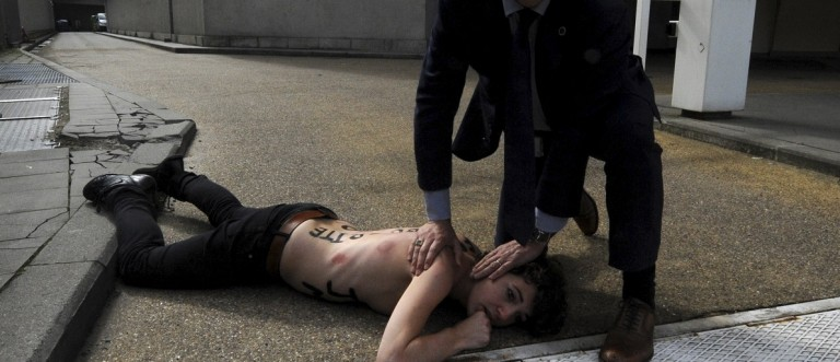 Activist Frutier from FEMEN is detained by security personnel after staging protest near European Commission in Brussels