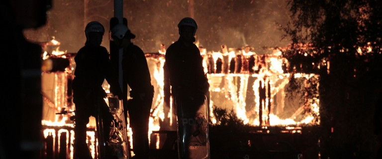 Police watches a fire burning at an asyl