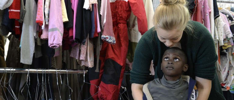 """A helper puts a jacket at a refugee boy at the """"Bayernkaserne"""", where clothes for migrants have been collected, in Munich, southern Germany, on September 9, 2015. (CHRISTOF STACHE/AFP/Getty Images)"""