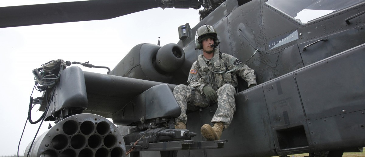 U.S. soldier Adam Elkins, Chief Warrant Officer of 4th Aviation Attack Battalion 2nd Combat Aviation Brigade, sits on an AH-64D Apache attack helicopter as he waits for a live-fire drill at a U.S. air base in Gunsan, about 270 km (168 miles) south of Seoul, July 21, 2009. REUTERS/Jo Yong-Hak