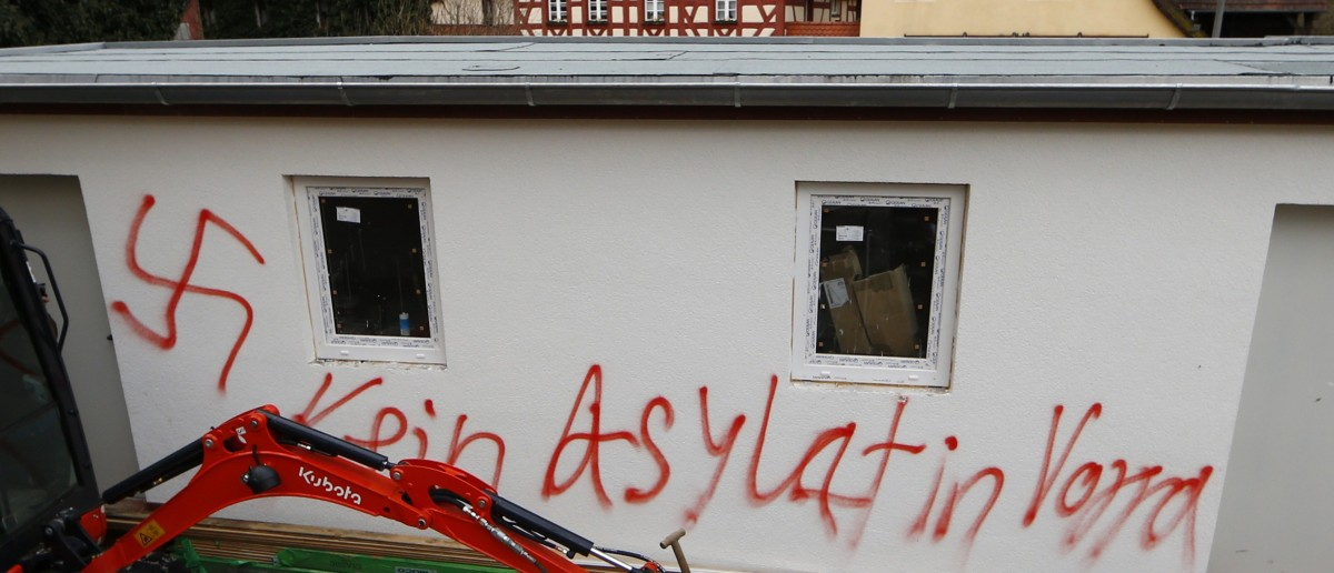 """A graffiti and a swastika are painted on a wall of a house in the municipality of Vorra near the northern Bavarian city of Nueremberg December 12, 2014. Three houses which were planned to be used for asylum seekers from early 2015 onwards, were set on fire and scrawled with Nazi symbols last night. The graffiti reads """"No asylum seekers in Vorra"""". REUTERS/Michael Dalder"""