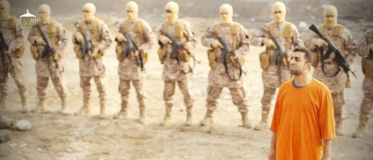 A man purported to be Islamic State captive Jordanian pilot Muath al-Kasaesbeh (in orange jumpsuit) stands in front of armed men in this still image from an undated video filmed from an undisclosed location made available on social media on February 3, 2015. Islamic State militants released the video on Tuesday purporting to show Kasaesbeh being burnt alive, and Jordanian state television said he was murdered a month ago. Reuters could not immediately confirm the video, which showed a man resembling the captive pilot standing in a black cage before being set ablaze. REUTERS/Social media via Reuters