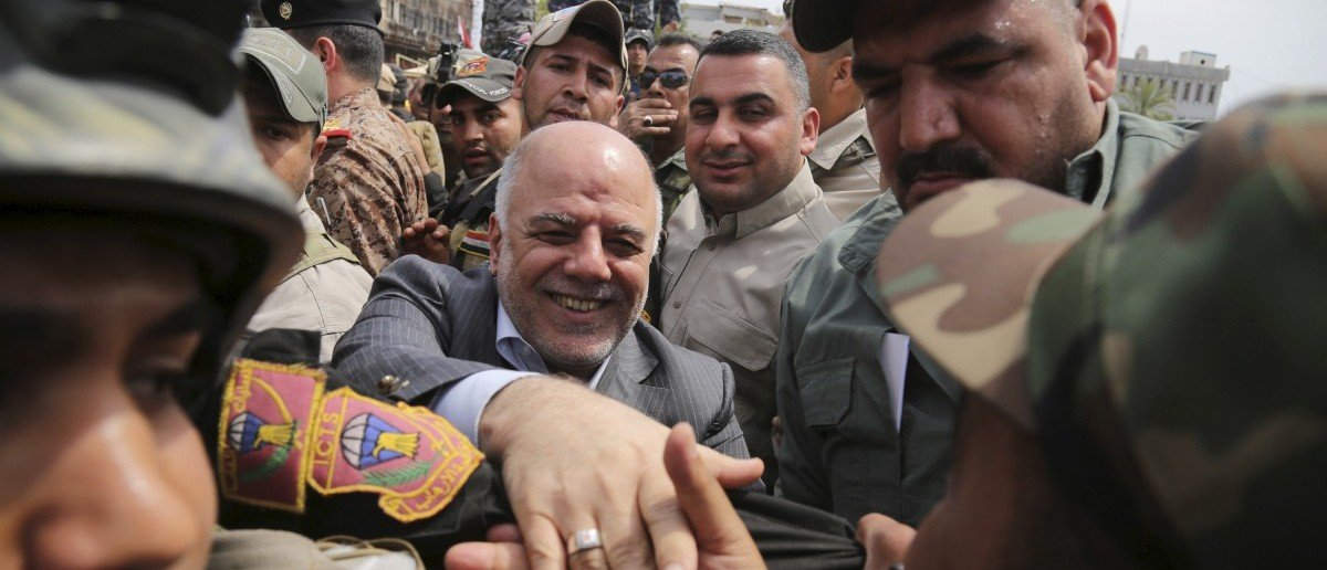 Iraq's Prime Minister Haidar al-Abadi (C) tours the city of Tikrit after Iraq security forces regained control from Islamist State militants, April 1, 2015. Iraqi troops and Shi'ite paramilitary fighters were battling Islamic State on Wednesday in northern Tikrit, which officials described as the Sunni Muslim militant group's last stronghold in the city. REUTERS/Stringer