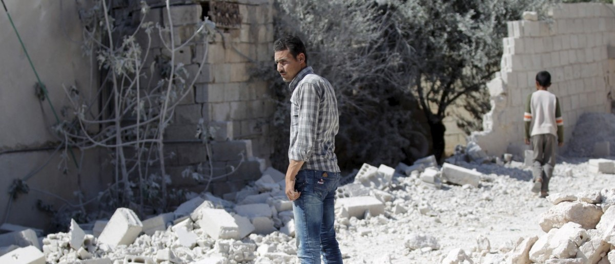 A man inspects the damage at a site hit by an airstrike in the rebel-controlled area of Jarjnaz village in Idlib province, Syria April 4, 2016. REUTERS/Khalil Ashawi
