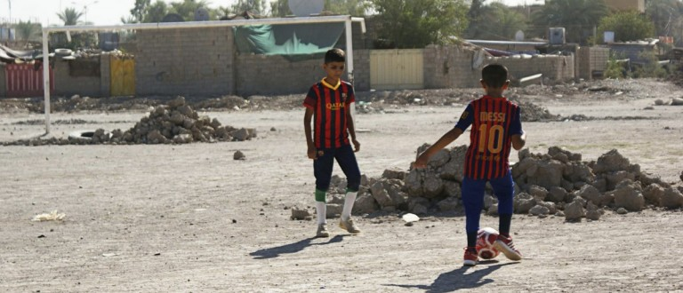 Boys play soccer in an abandoned soccer pitch in Baquba about 50 km (31 miles) northeast of Baghdad, August 6, 2013. Iraqis have endured extreme violence for years, but since the since the start of 2013 the intensity of attacks on civilians has dramatically increased, reversing a trend that had seen the country grow more peaceful. Attacks have spread to some of the few places left for public entertainment such as cafes and public soccer pitches, turning Baghdad into a giant fortified prison of concrete blast walls, where once again few now dare to socialise in public. Police dug up the pitch as a security measure to prevent youths from playing there. REUTERS/Mohammed Adnan