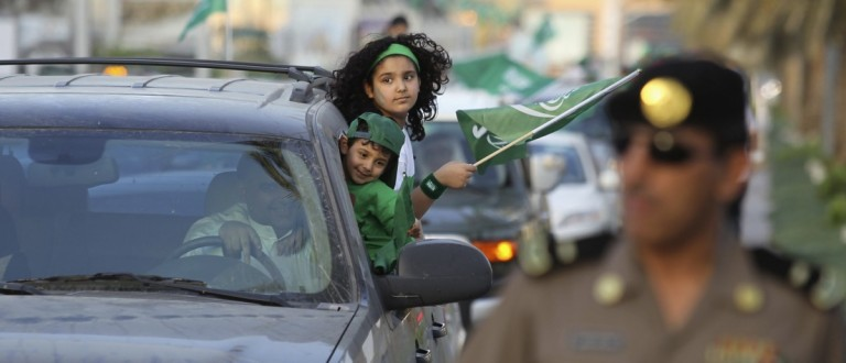 A girl waves Saudi Arabia's national flag as she rides a car, as the oil-rich Gulf Arab country celebrates its National Day, in Riyadh September 23, 2013. REUTERS/Faisal Al Nasser