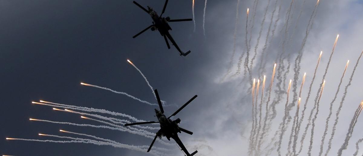 "A Mi-28N (top) from the Berkuty (Golden Eagles) helicopter display team flies in formation during a performance before its hard touchdown at the ""Aviadarts"" military aviation competition at the Dubrovichi range near Ryazan, Russia, August 2, 2015. The aircraft started dipping down due to back propeller failure and crashed, killing one of two pilots, according to a Reuters photographer and official representatives of the competition. The aviation contest is part of the International Army Games, which are held in Russia from the 1st till the 15th of August with participants from 17 countries, according to organizers. REUTERS/Maxim Shemetov  - RTX1MQ2D"