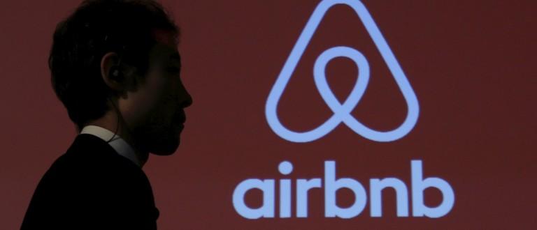 A man walks past a logo of Airbnb (REUTERS/Yuya Shino)