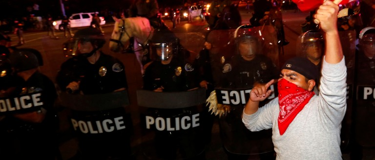 Police in riot gear form a line to break up a group of protesters, one of whom is carrying a Mexican flag, outside Donald Trump's campaign rally in Costa Mesa, California