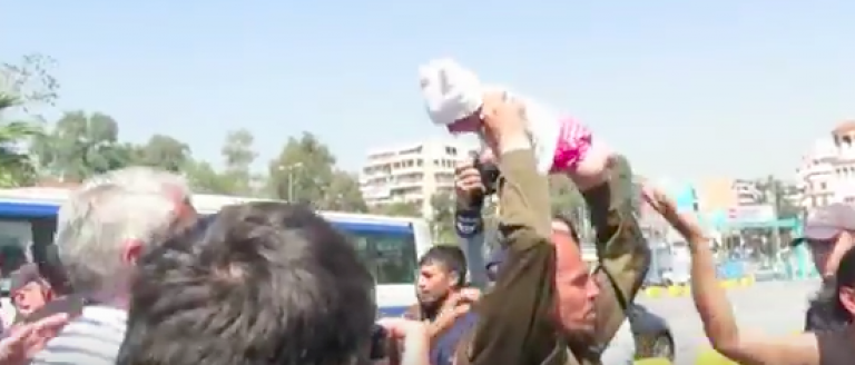 A migrant attempts to throw a baby at police. (YouTube Screen shot)