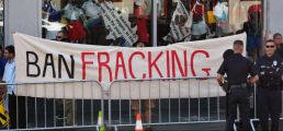 """Two policemen stand guard as anti-fracking wave a banner that reads: """"Ban Fracking"""" during a demonstration in Hollywood, Calif. (Dan Holm / Shutterstock.com)"""
