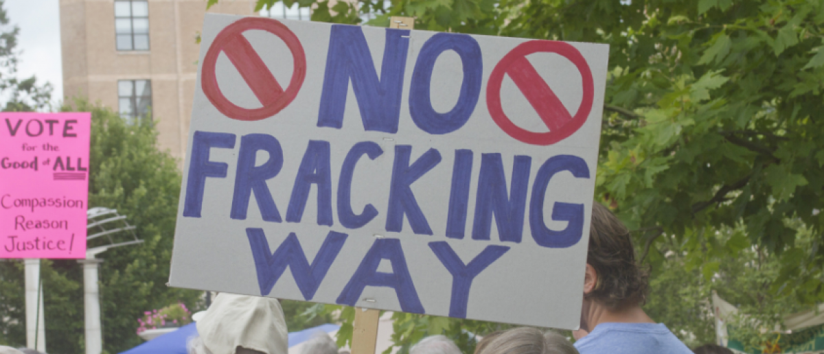 August 4, 2014: Woman at a Moral Monday rally holds a sign protesting fracking amid a gathering crowd of demonstrators on August 4, 2014 in downtown Asheville, NC (J. Bicking / Shutterstock.com)