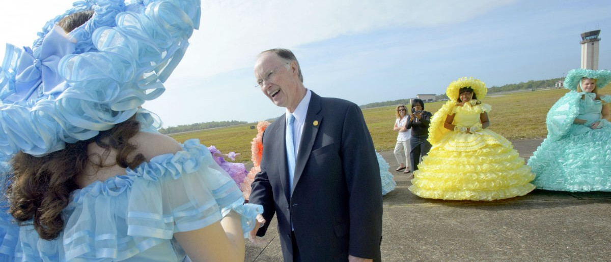 Robert J. Bentley, Governor of Alabama, enters the ground breaking ceremony for the Airbus A320 at Brookley Aeroplex as ladies with the Mobile Azalea Trail Maids greet him in Mobile, Alabama on April 8, 2013. (Photo: Matthew HINTON/AFP/Getty Images)
