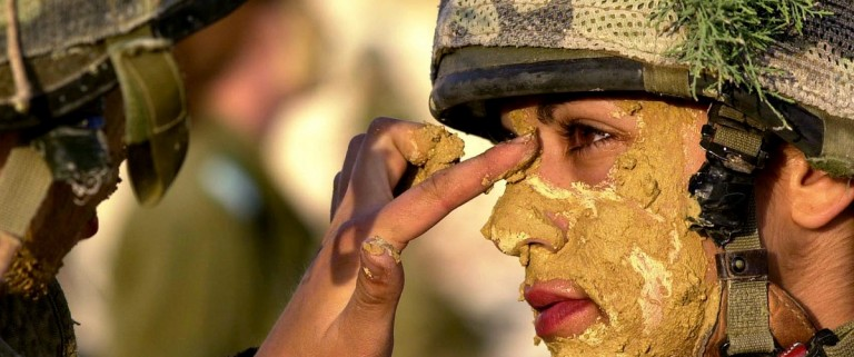 In a picture released on May 23, 2005 by the Israeli Defence Forces shows an Israeli army female soldier painting the face of a comrade with mud prior to a week-long survival course for women in the infantry at an undisclosed location in Israel. REUTERS/IDF/HO OP/TW - RTRC754