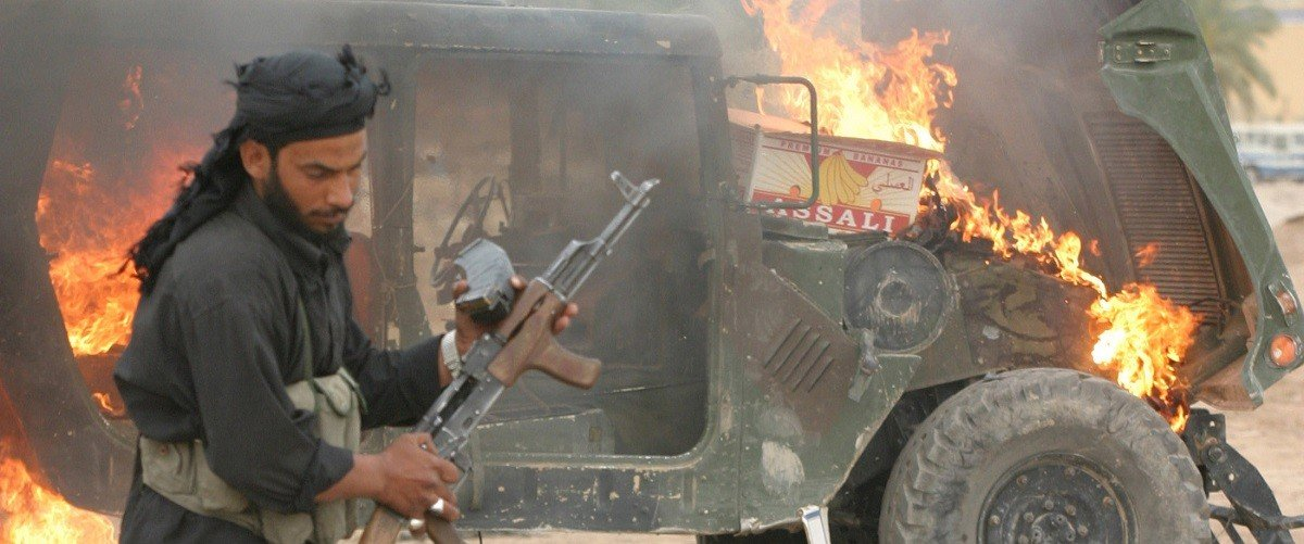 File photo showing an Iraqi militiaman walking past a burning U.S. Army Humvee vehicle, which was captured during a morning gun battle and later set alight, in the town of Kufa on April 19, 2004. Faced with continuing attacks on U.S. troops in Iraq and Afghanistan, Army generals on Tuesday urged defense contractors to step forward with creative solutions to build better combat vehicles. Armor-reinforced Humvees and trucks in maintenance convoys remain vulnerable to attacks by roadside bombs and rocket-propelled grenades, even though the U.S. military has already rushed to retrofit its equipment with additional armor and other protective gear. REUTERS/Ceerwan Aziz.