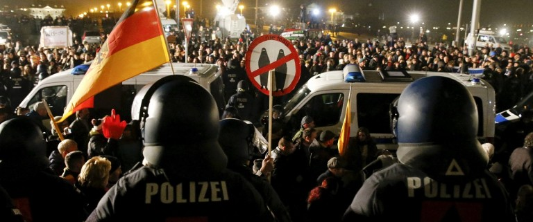 People attending an anti-immigration demonstration organised by PEGIDA walk past opponents of PEGIDA behind police cars, in Dresden