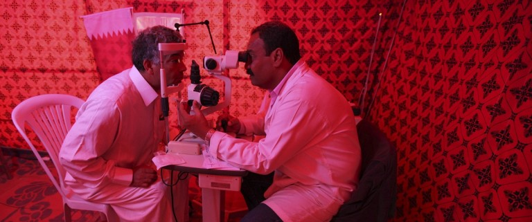 An ophthalmologist examines the eyes of a Libyan refugee in a makeshift hospital tent at a refugee camp in Tataouine