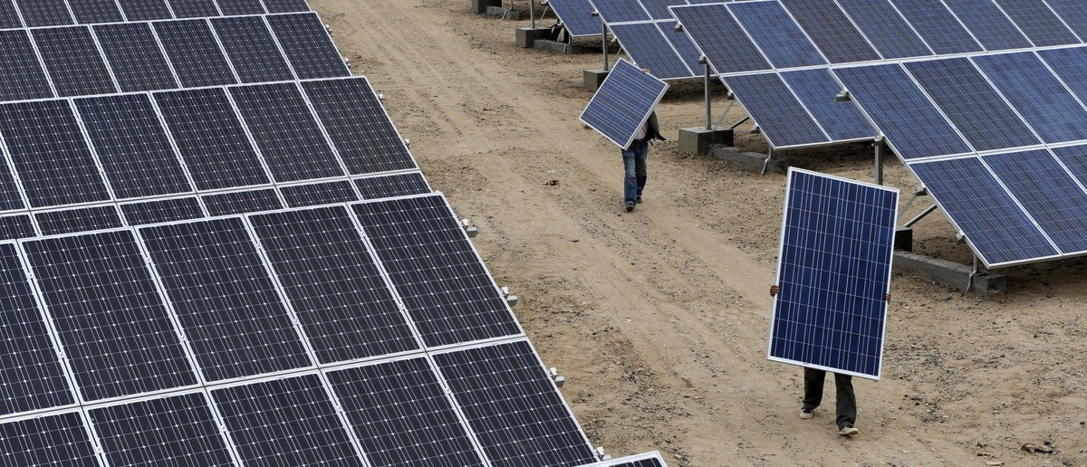 Employees carry solar panels at a solar power plant in Aksu, Xinjiang Uyghur Autonomous Region May 18, 2012. The United States hit Chinese solar companies with punitive import tariffs of 30 percent or more on Thursday, ruling they had dumped cut-price solar panels on the U.S. market. REUTERS/Stringer